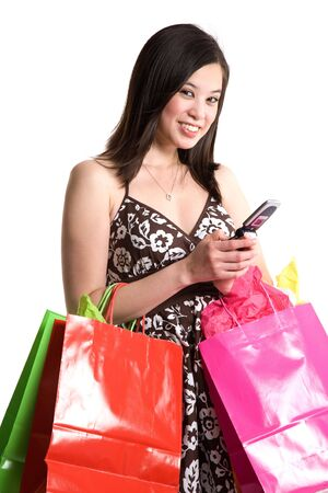 An isolated shot of a beautiful asian woman shopping and texting messages Imagens
