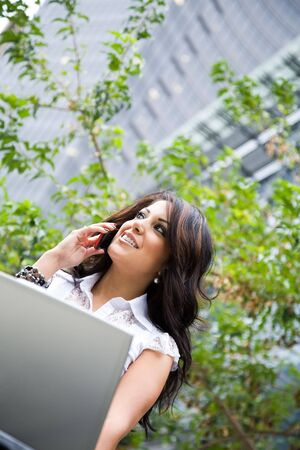 A hispanic businesswoman working on her laptop and talking on the phone photo
