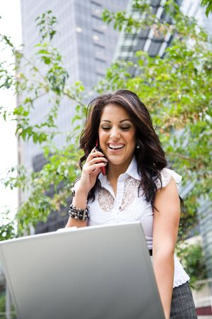 A beautiful hispanic businesswoman working on her laptop and talking on the phone photo