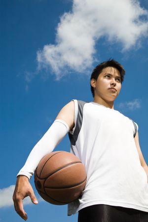 야외 농구를 들고 아시아 농구 선수의 총