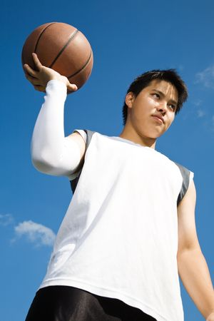 A shot of an asian basketball player holding a basketball photo