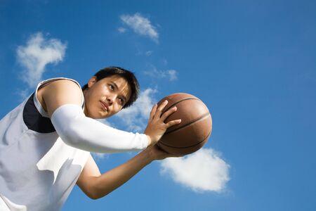 A young asian basketball player shooting a basketball photo