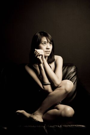 A portrait of a beautiful asian woman sitting on a couch photo