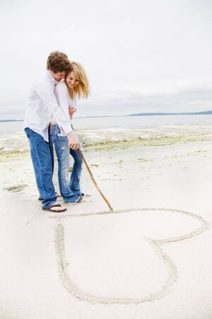 A caucasian couple in love drawing a heart sign on the beach photo
