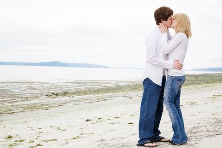 A caucasian couple in love kissing on the beach photo
