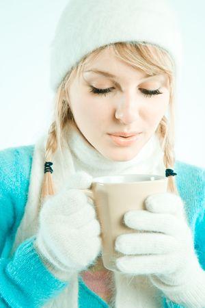 A beautiful caucasian blonde girl drinking hot coffee photo