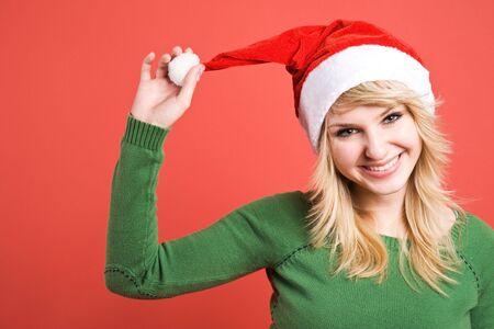 wearing santa hat: A beautiful happy caucasian girl wearing santa hat during christmas
