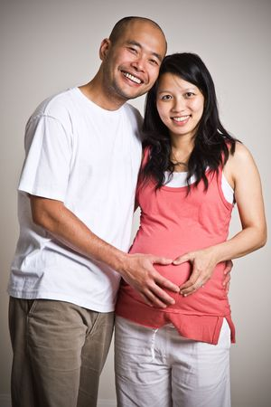 A happy pregnant asian couple expecting their  photo