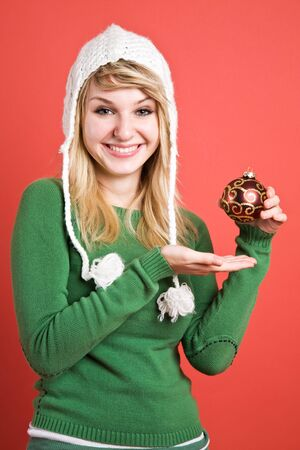 A beautiful caucasian girl holding a christmas ornament