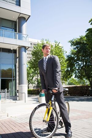 A caucasian businessman riding a bike to work photo