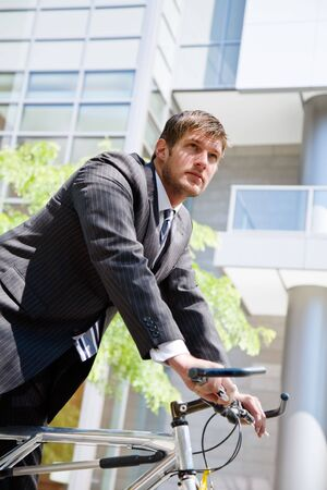 A caucasian businessman riding a bike to work, can be used for green or gas savings concept photo