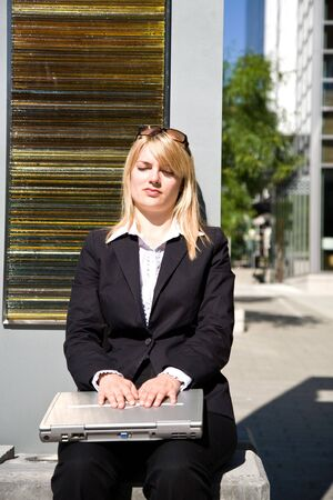 A caucasian businesswoman taking a break and relaxing outside the office photo