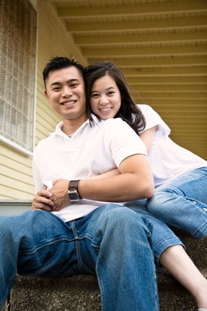 A happy asian couple sitting on the porch in front of their house Stock Photo
