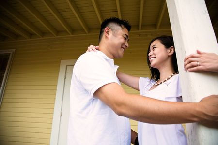 A shot of a happy asian couple standing in front of the house photo