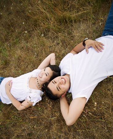 A happy asian couple lying down on the grass