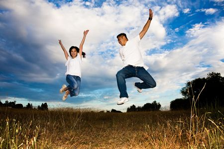 girl bonding: A shot of a happy asian couple jumping for joy Stock Photo