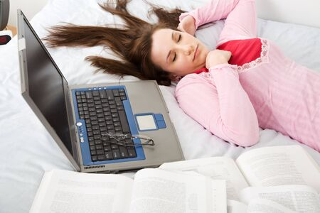 A caucasian female student falls asleep while studying photo