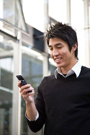 A casual asian businessman texting messages on his cellphone photo