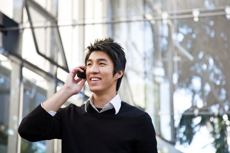 businessman talking: A casual asian businessman talking on the phone