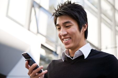 mobile communication: A casual asian businessman texting on his cell phone