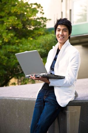 An asian college student holding a laptop at the campus photo
