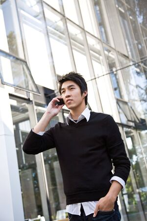 chat: A shot of a casual asian businessman talking on the phone