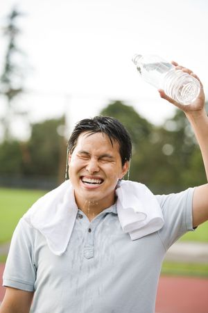 A young active sporty asian male cooling down by pouring water on top of his head after exercise Archivio Fotografico