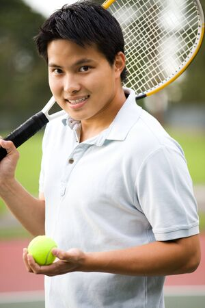 playing tennis: A young sporty casual asian male playing tennis Stock Photo
