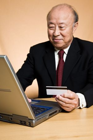 A senior asian businessman shopping online using his laptop photo