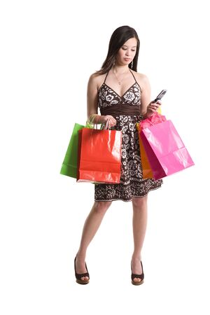 A beautiful asian woman carrying shopping bags calling on the phone  photo