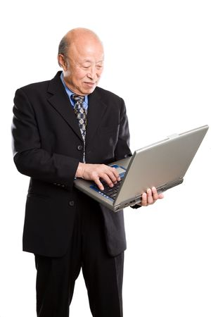 A senior asian businessman typing on a laptop photo