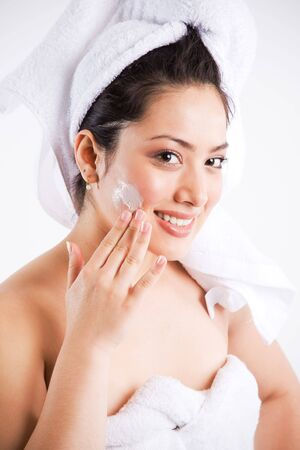 A beautiful asian woman putting on lotion on her face photo