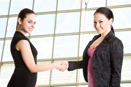 Two businesswomen shaking hands in the office photo