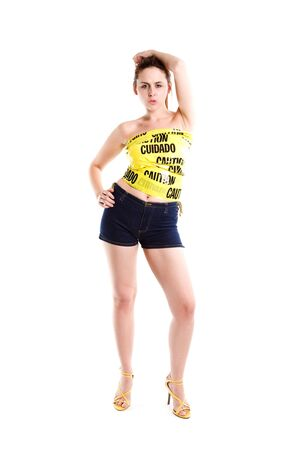 An isolated shot of a sexy caucasian woman wrapped in caution tape Stock Photo
