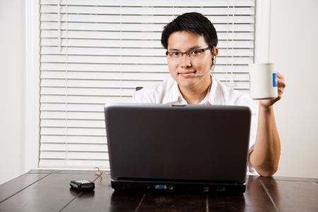 working: An asian entrepreneur working on his laptop from home