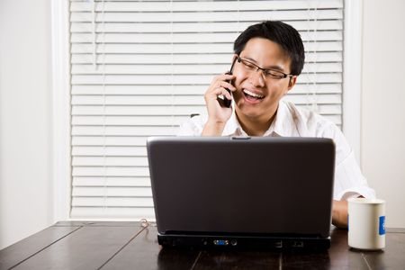 An asian entrepreneur talking on the phone working from home photo