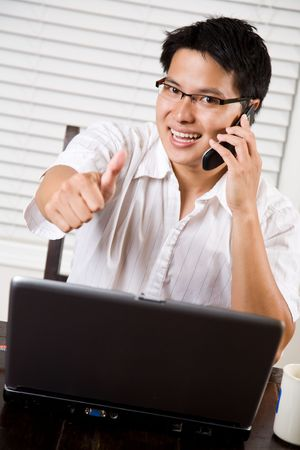 An asian entrepreneur businessman giving a thumbs up photo