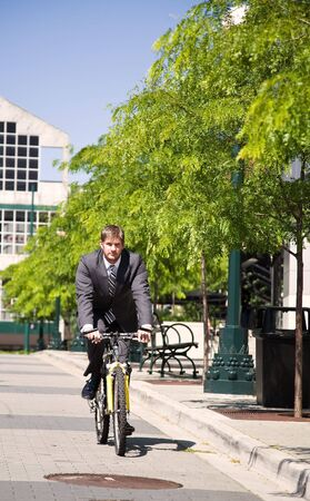 A caucasian businessman riding a bicycle to work, can be used for green or gas savings concept Stock Photo - 3720739
