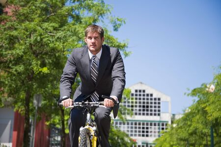 A caucasian businessman riding a bicycle to work, can be used for gas savings concept photo
