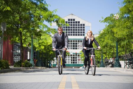 Two business people riding bicycle to work, can be used for gas savings concept photo