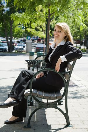 A caucasian businesswoman sitting on a bench outdoor photo