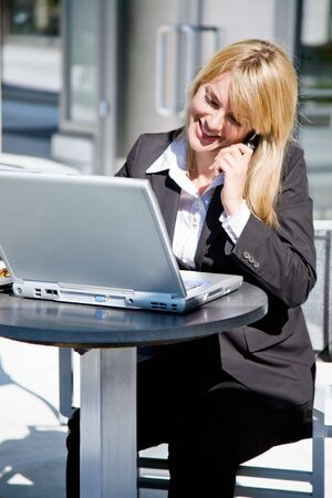 A caucasian businesswoman talking on the phone while working on her laptop photo