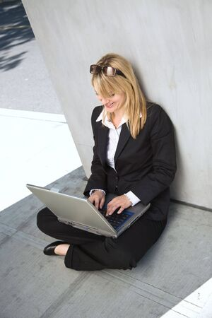 A caucasian businesswoman working on her laptop outdoor photo