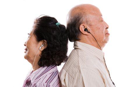 音楽を聴く上級アジア カップルの分離のショット 写真素材