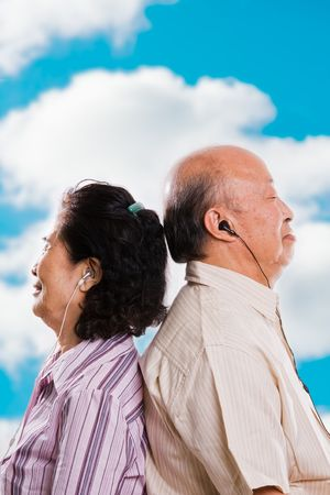 A happy senior asian couple listening to music outdoor photo
