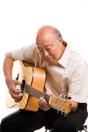 An isolated shot of a senior asian man playing guitar photo