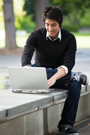 An asian student working on his laptop on campus Stock Photo - 3753622
