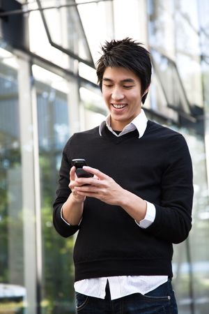 mobile communication: An asian man texting on the cellphone
