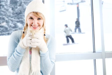 winter fashion: A beautiful caucasian girl drinking hot coffee at a ski resort