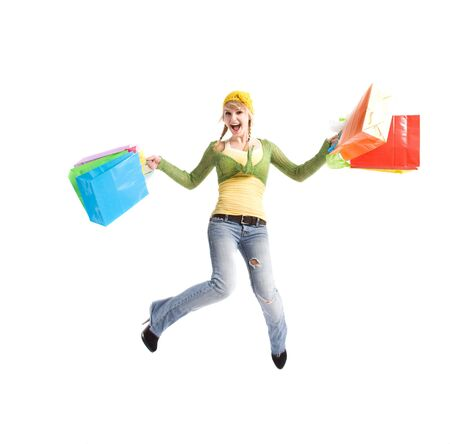 A beautiful happy caucasian girl jumping and carrying shopping bags photo